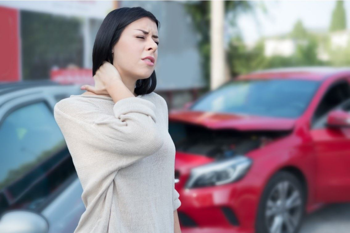 woman rubbing her injured neck after a car accident
